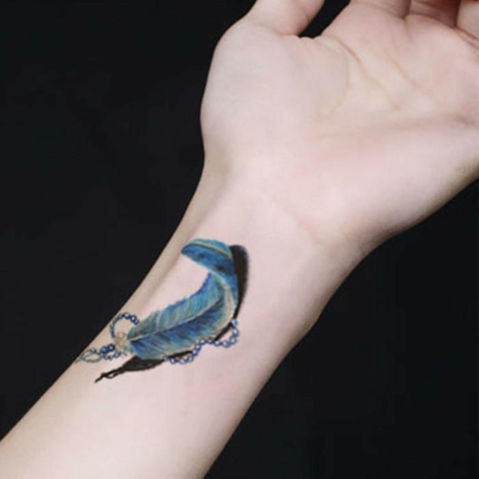 Tattoo polso, tatuaggio con disegno di una piuma, disegno colorato sul polso della mano