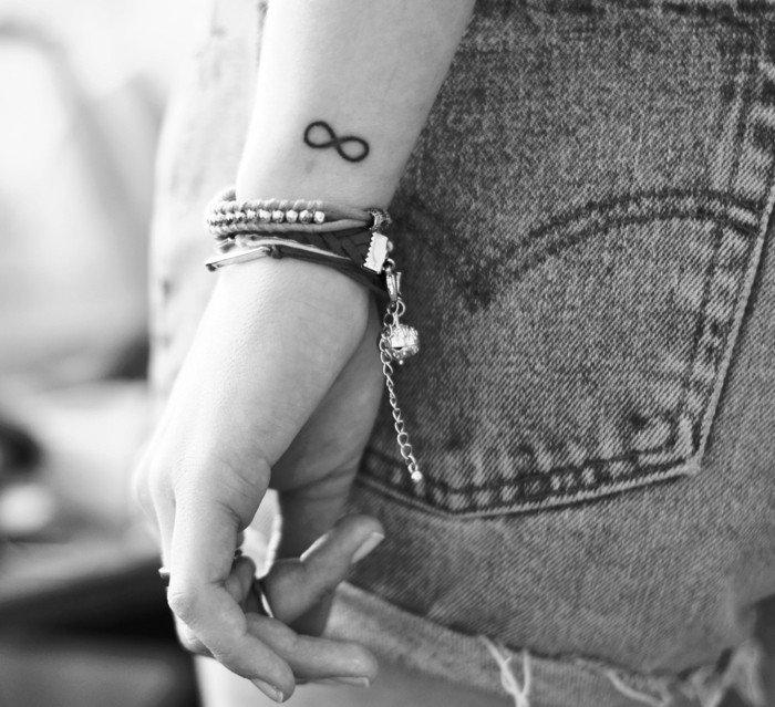 Simboli tatuaggi, tattoo infinito sul polso della mano, donna con braccialetti