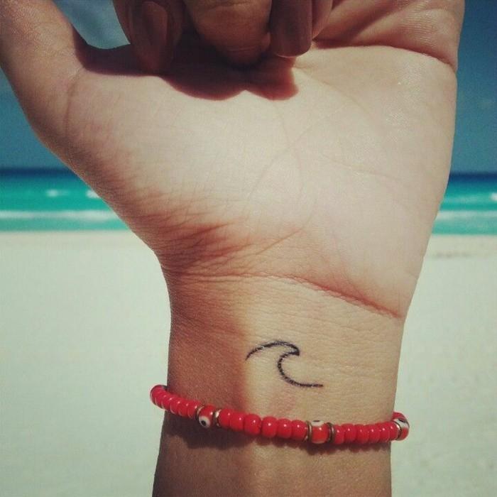 Disegno onda del mare, tatuaggio polso della mano, braccialetto rosso con portafortuna