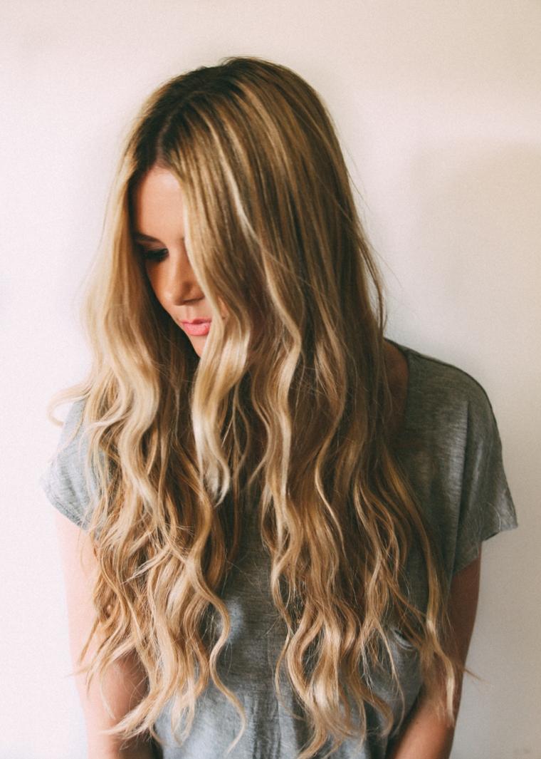 Ragazza con capelli biondi, capelli lunghi e ricci, abbigliamento con maglietta grigia