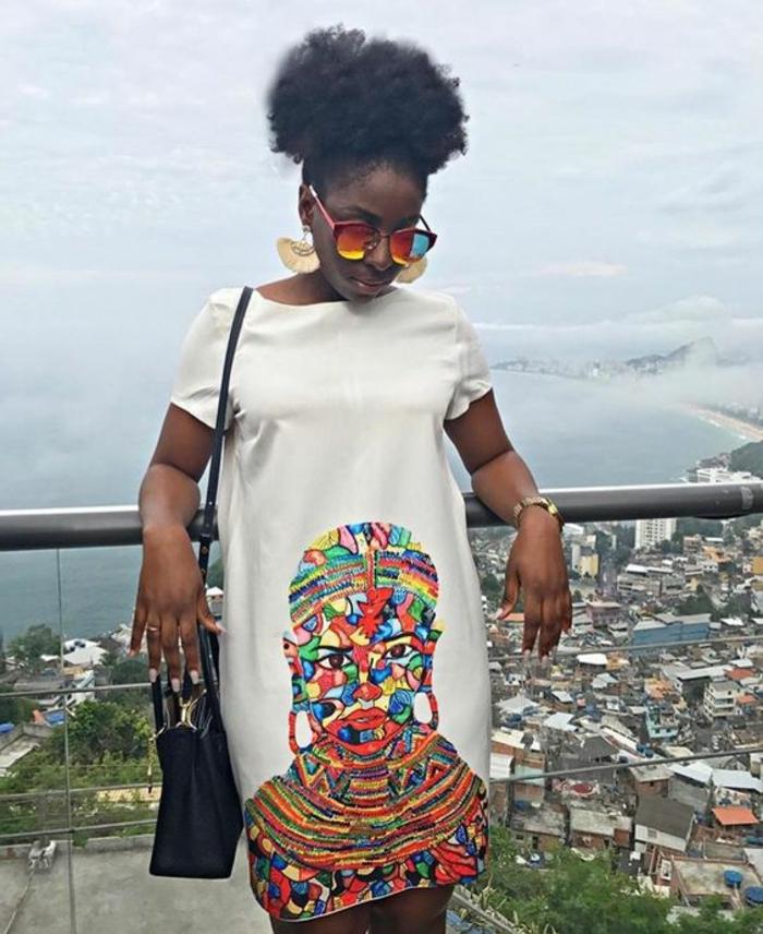 Tessuti africani on disegni colorati, ragazza con capelli ricci, vestito bianco fino al ginocchio