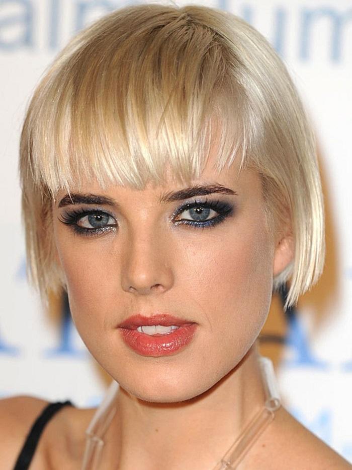 Donna con capelli biondi, taglio caschetto corto con frangia, viso truccato con occhi azzurri