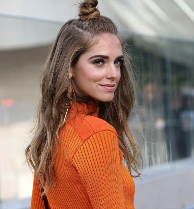 Acconciature capelli media lunghezza, ragazza bionda con chignon, maglietta colore arancione