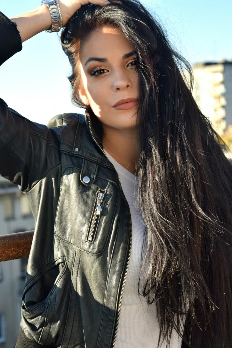 Ragazza con capelli neri, capelli lunghi e mossi, abbigliamento con giacca