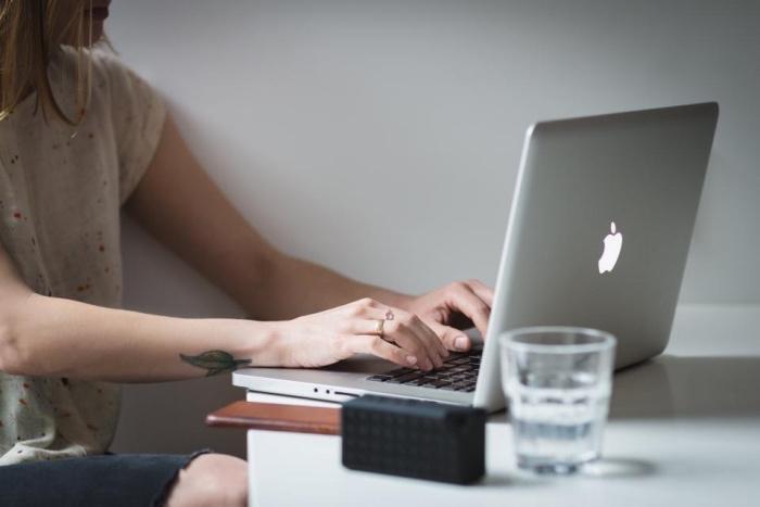 Tattoo scritte braccio, donna che scrive al computer, tattoo sul polso