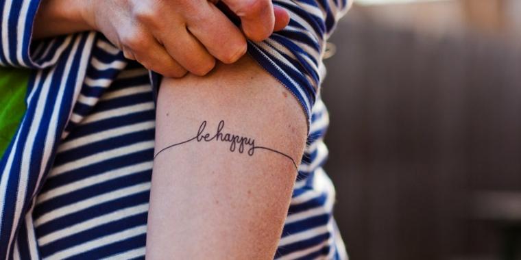 Scritte tattoo in inglese, be happy in corsivo, tatuaggio sull'avambraccio