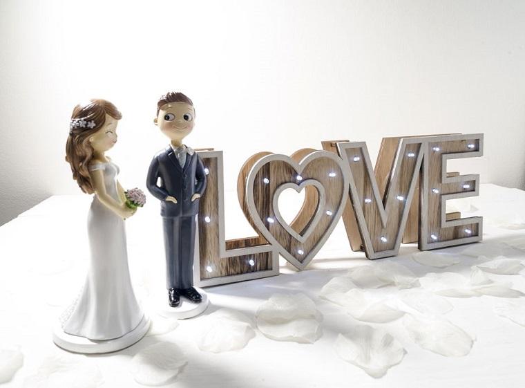 Petali bianchi di rosa, scritta luminosa Love, statuine sposi