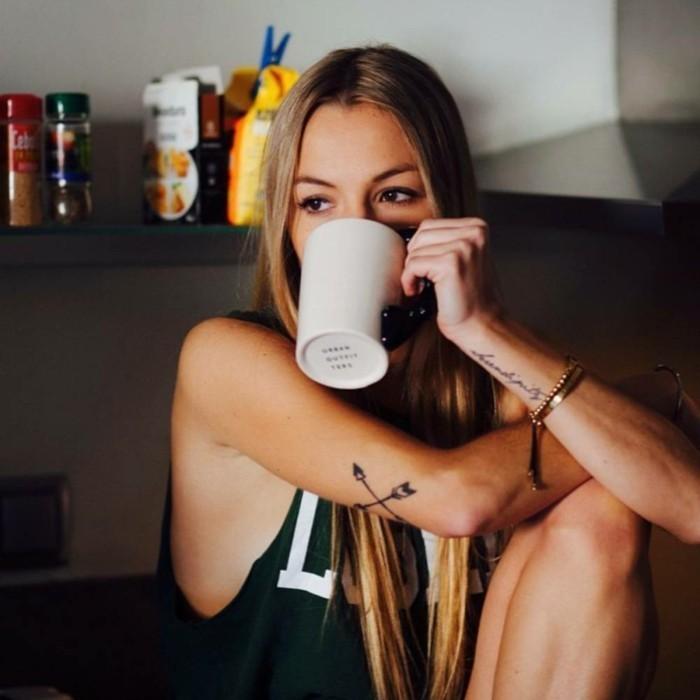 Donna che beve il caffè, tatuaggio piccolo sul polso, ragazza con capelli biondi