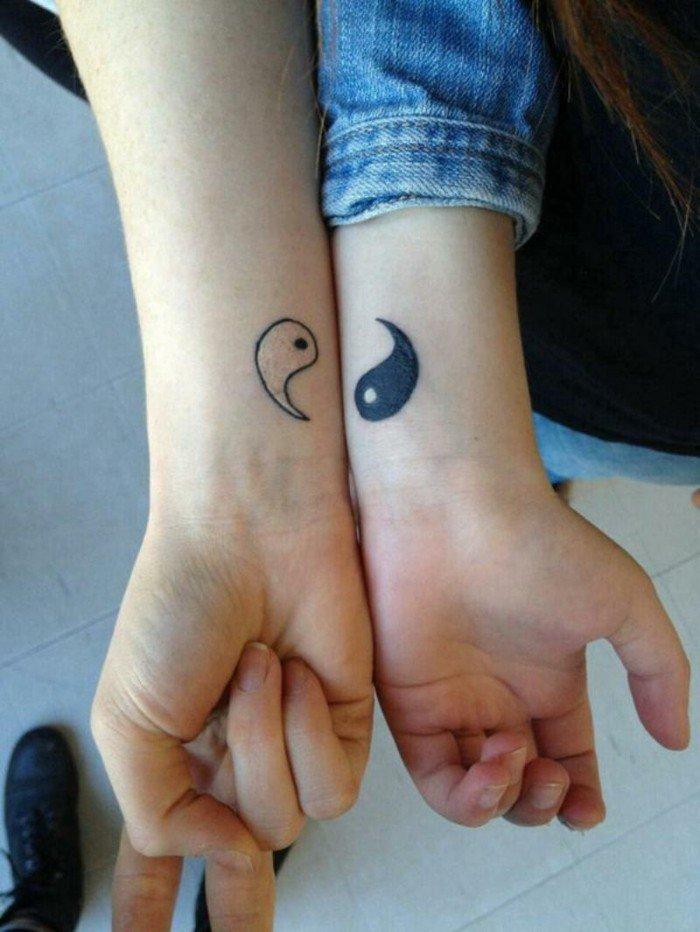 Simbolo Yin e Yang sui polsi delle mani, tatuaggio simbolico sulle braccia
