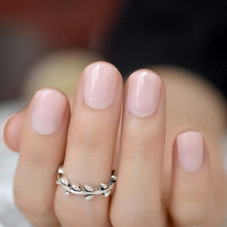 Unghie di colore rosa tenue, manicure con unghie corte, anello in oro bianco