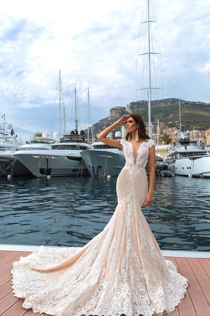 Ragazza con abito da sposa, vestito color crema in pizzo, porto con barche