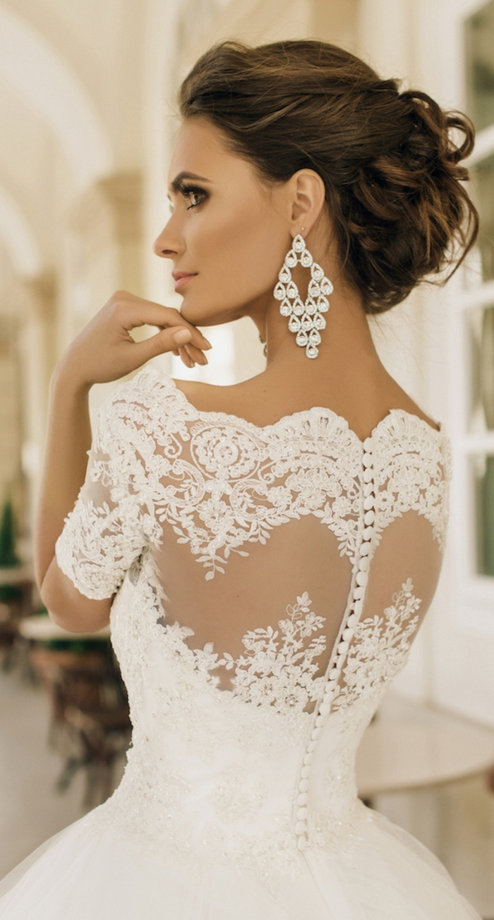 Vestito da sposa con ricami, capelli castani legati, abito con ornamenti floreali