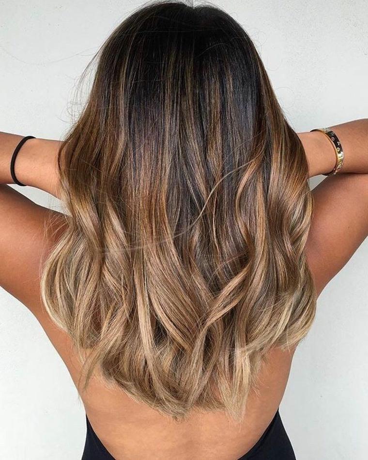 Ragazza con capelli ricci, colore capelli balayge, mani fra i capelli