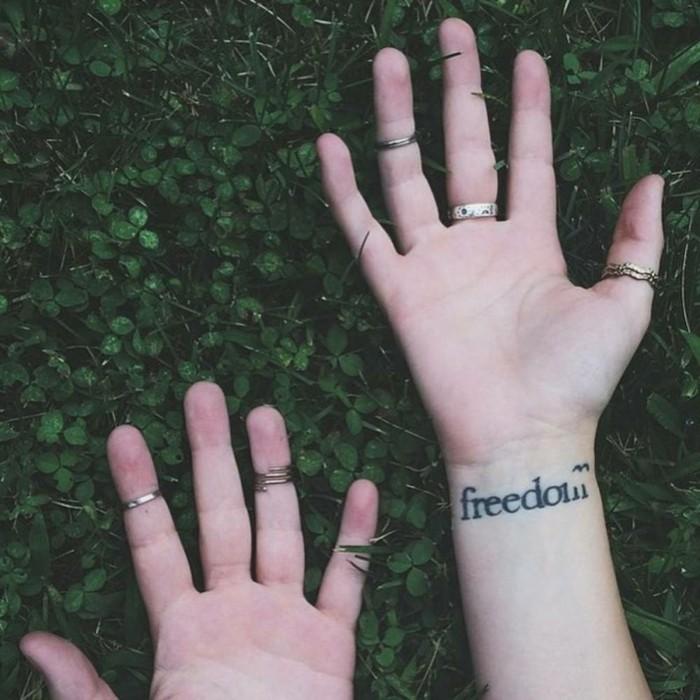 Tatuaggio con scritta sul polso, tattoo freedom in inglese, mani ragazza con anelli