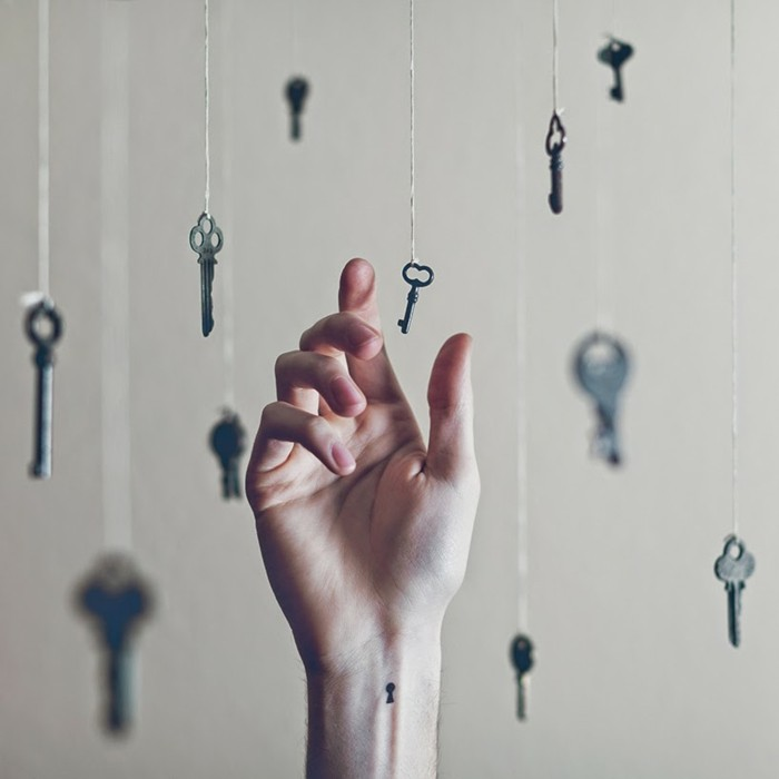 Tattoo polso, disegno imbuco chiave sul braccio di una donna, chiavi appese su dei fili