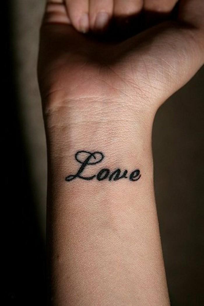 Tatuaggio con scritta in inglese, tattoo Love sul polso della mano, pungo di una ragazza