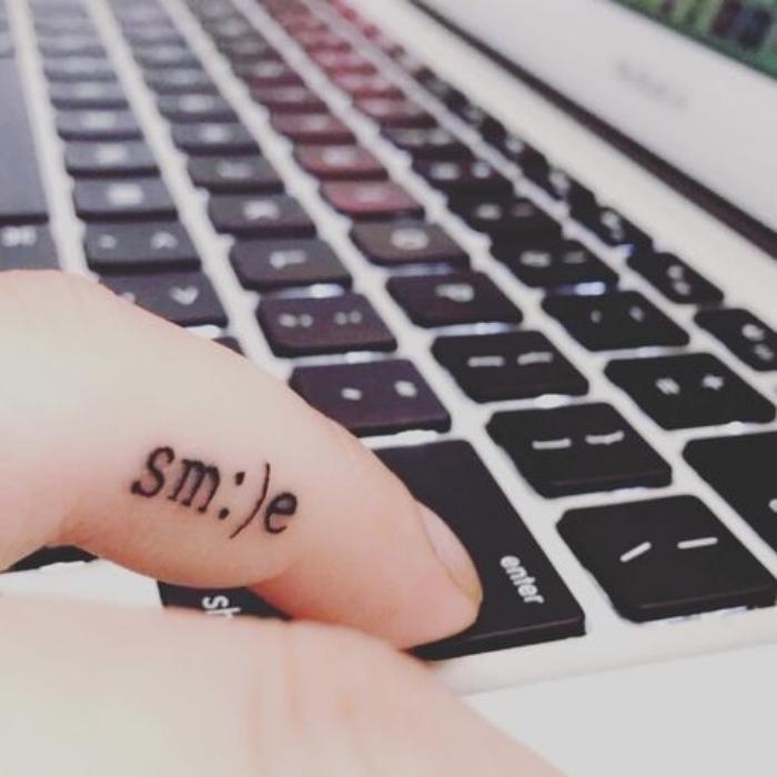 Tatuaggio sul dito, tattoo scritta smile, tastiera del computer