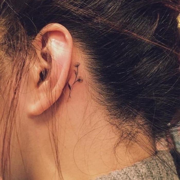 Tatuaggio dietro l'orecchio, tattoo disegno fiore, donna con capelli legati