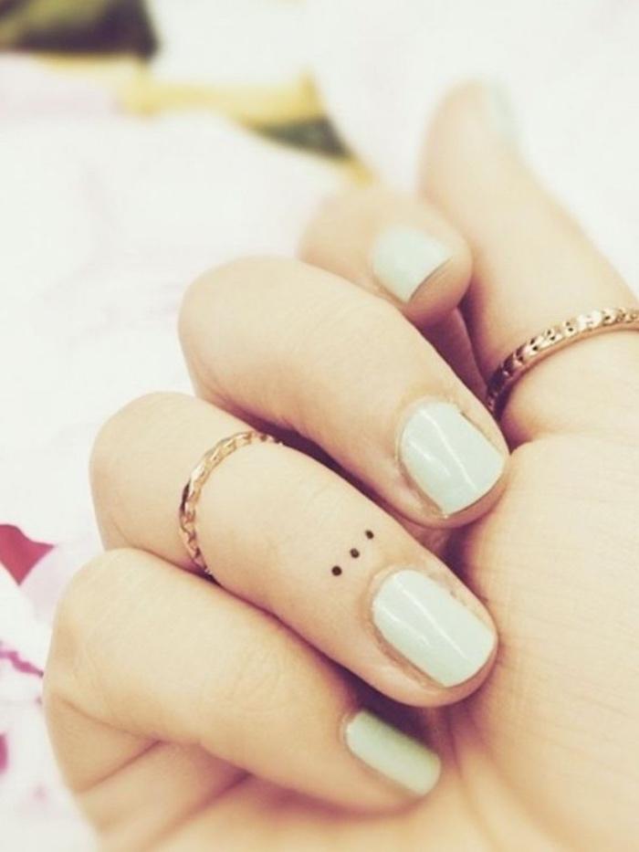 Donna con smalto bianco, anelli in oro, tatuaggio con puntini