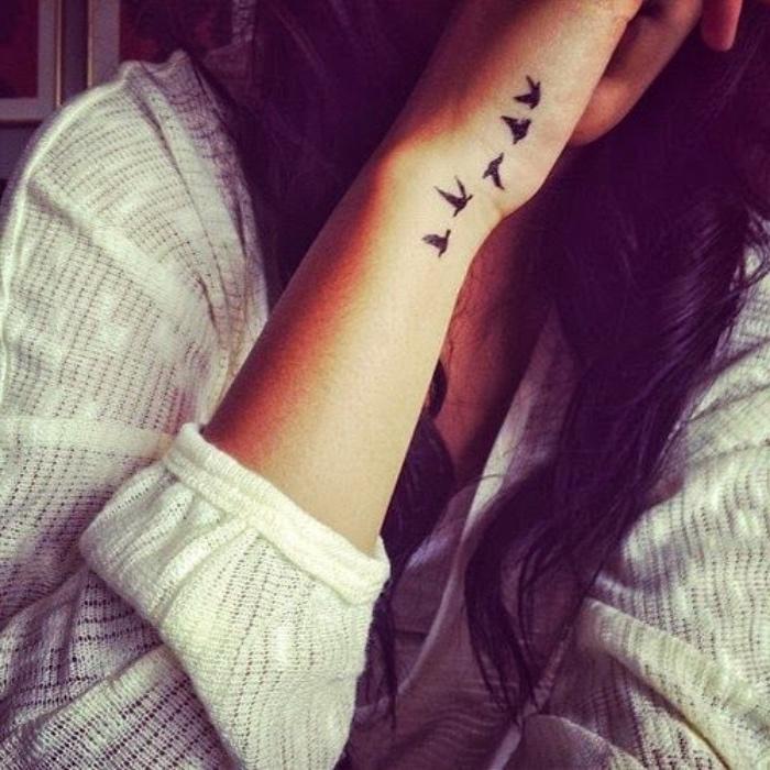 Tatuaggio con uccelli, tattoo sul polso, donna con capelli mossi