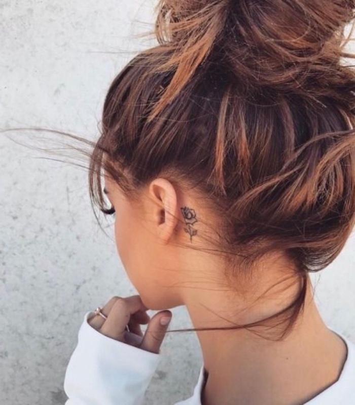 Ragazza con capelli castani, tatuaggi femminili eleganti, capelli legati a chignon