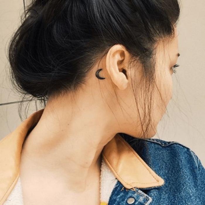 Tatuaggio dietro l'orecchio, disegno mezza luna, donna con capelli legati