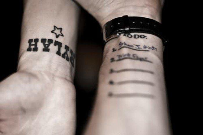Un uomo con tatuaggi sul braccio, tattoo uomo con scritte
