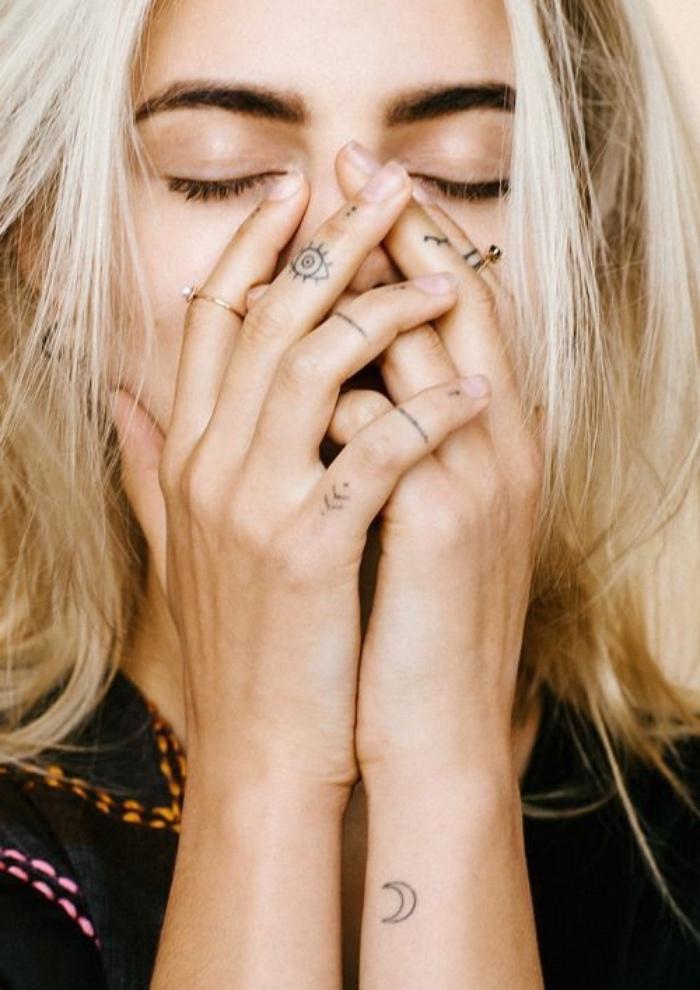 Tatuaggi più belli del mondo. donna con tattoo sulle dita, disegno mezza luna