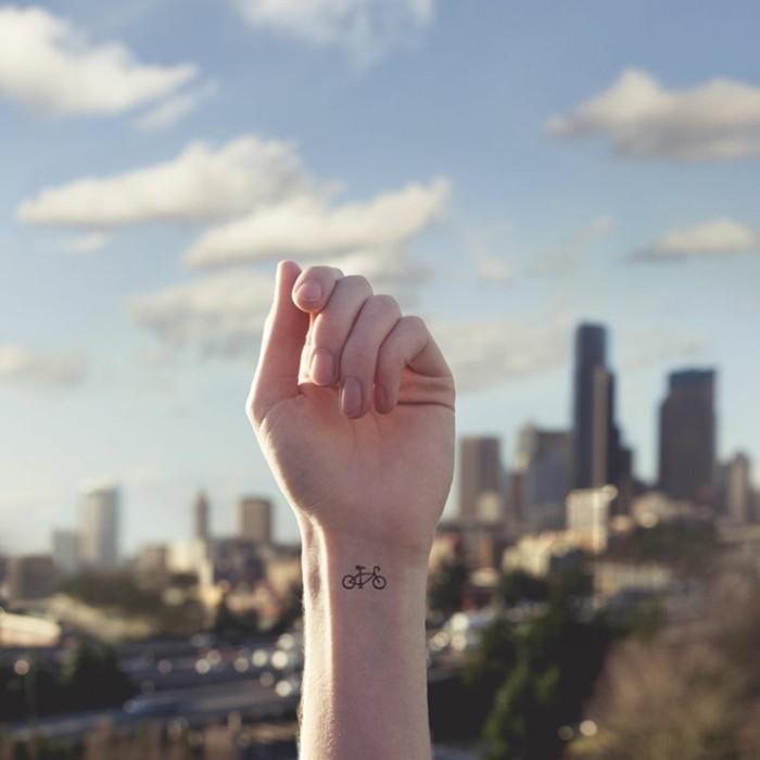 Simboli tatuaggi libertà, tattoo femminile sul polso, mano alzata di una donna