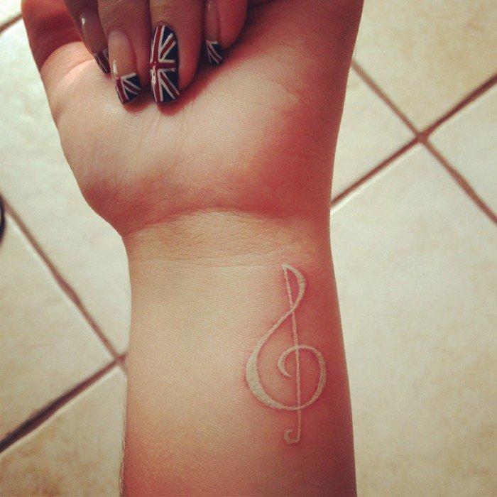 Tattoo nota musicale, tatuaggio invisibile sul polso, manicure con la bandiera della Gran Bretagna
