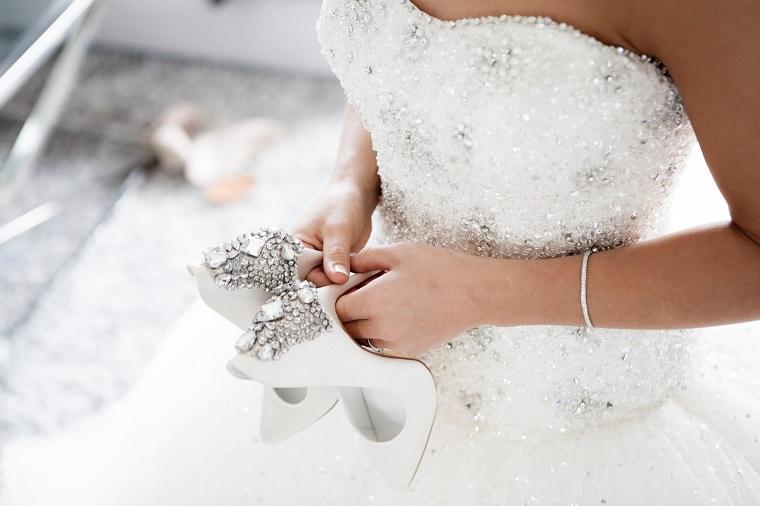 Abito da sposa con perle, scarpe da matrimonio con brillantini, preparativi matrimonio