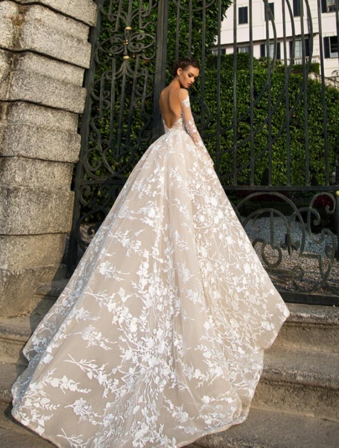 Abito da sposa con gonna lunga, vestito con ricami floreali, ragazza con capelli legati