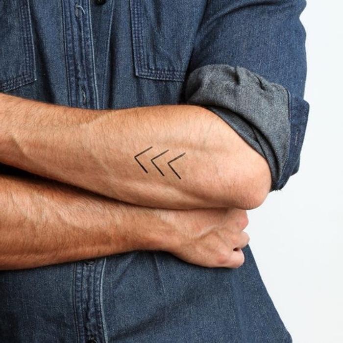Tattoo braccio uomo, disegno di tre frecce, camicia blu in jeans