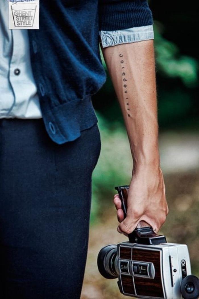 Tattoo scon scritta, tattoo sull'avambraccio, uomo con macchina fotografica