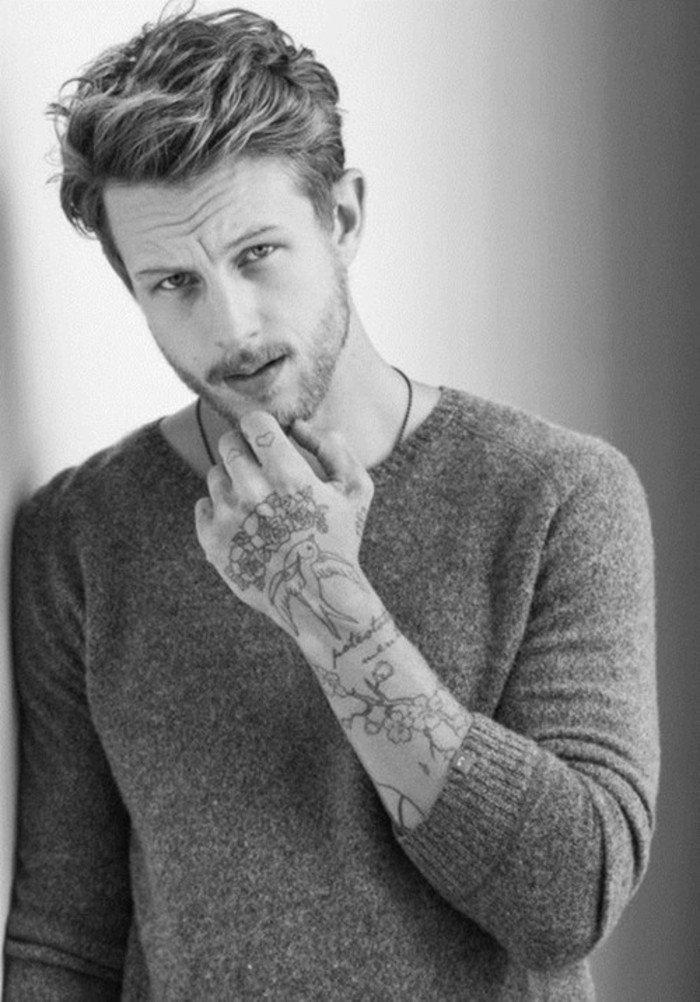 Ragazzo con capelli biondi, tatuaggio sul polso della mano, abbigliamento con maglietta grigia