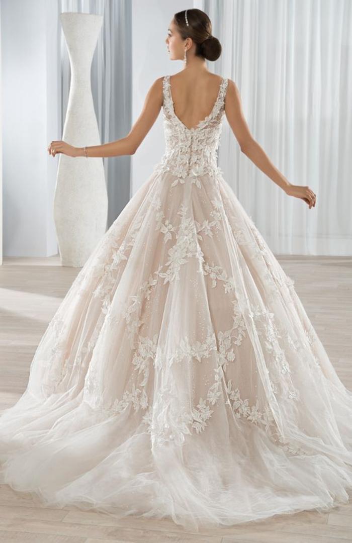 Abito da sposa con tulle, capelli legati a chignon, vestito in chiffon bianco