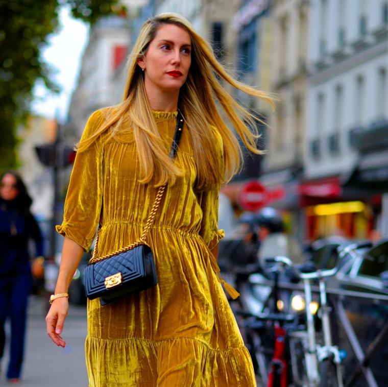 Ragazza che cammina, capelli biondi e lisci, abito giallo tessuto velvet, borsetta nera tracolla