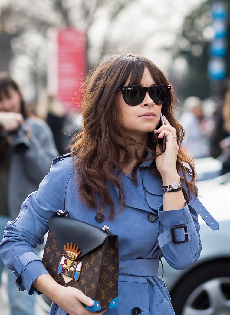 Donna con trench blu, capelli castani ricci, acconciatura con frangia