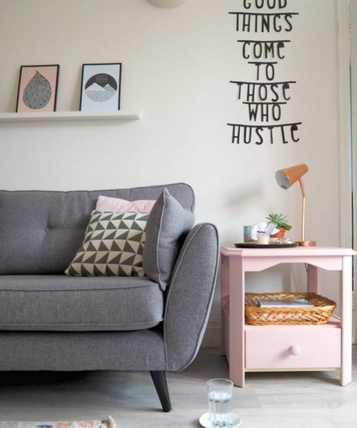 Soggiorno bianco e grigio, divano con cuscini, decorazione da parete con scritta