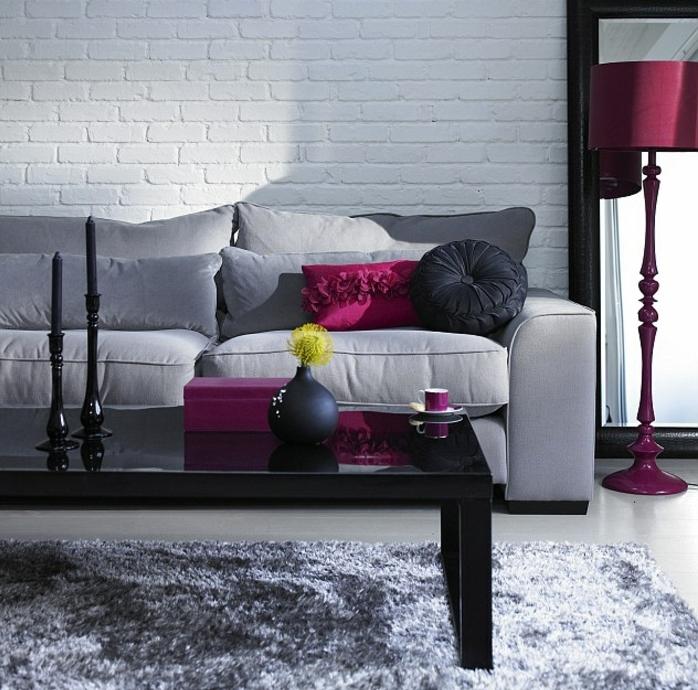 Soggiorno bianco e grigio, parete con pietre a vista, divano morbido con cuscini