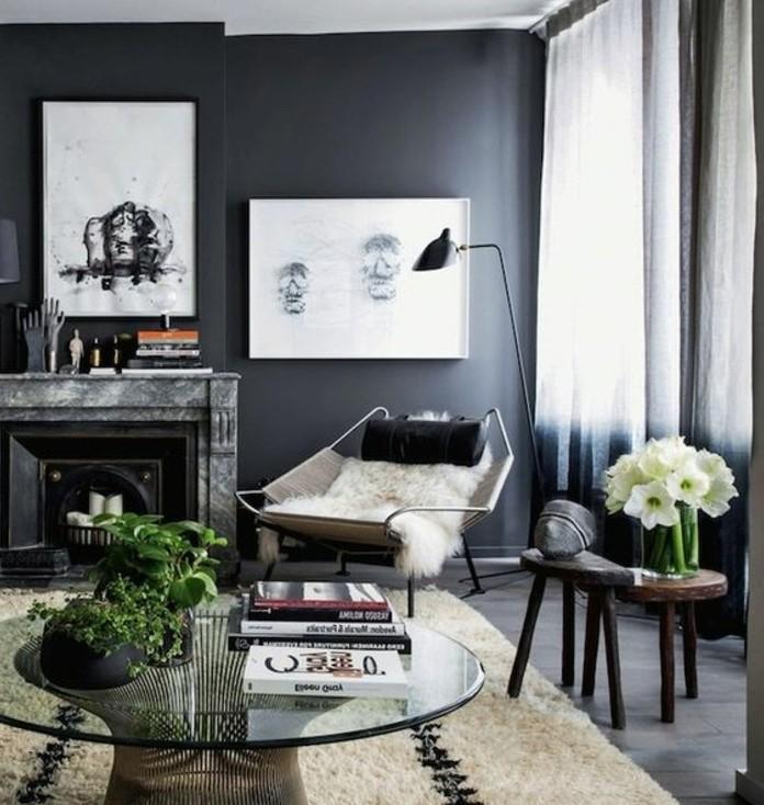 Idee arredamento soggiorno, parete di colore grigio, tavolino basso rotondo di vetro