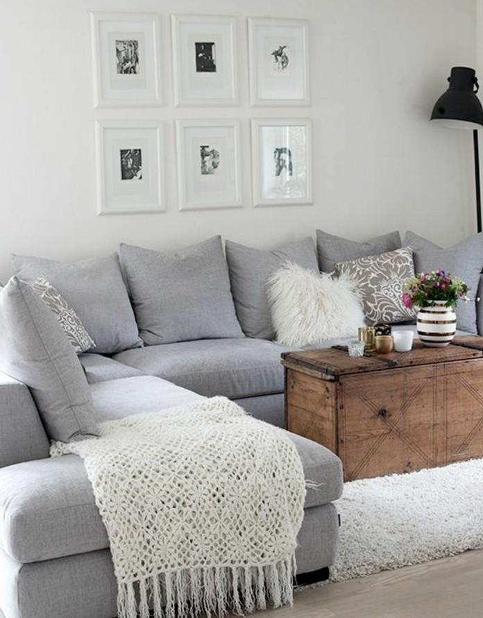 Idee arredamento soggiorno. divano angolare di colore grigio, tavolino di legno