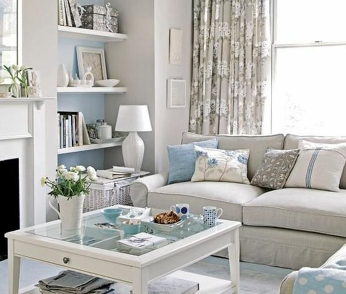 Mobili soggiorno moderni, parete di colore blu con mensole, tavolino basso di legno e vetro