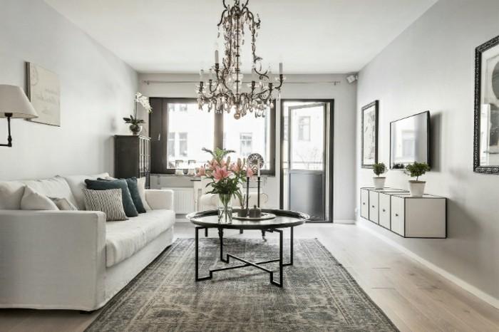Arredare salotto piccolo, divano di tessuto, tavolino rotondi di metallo, mobile bianco sospeso