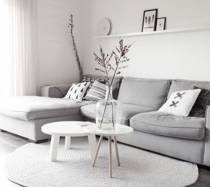 Mobili soggiorno moderni, divano di colore grigio, due tavolini rotondi