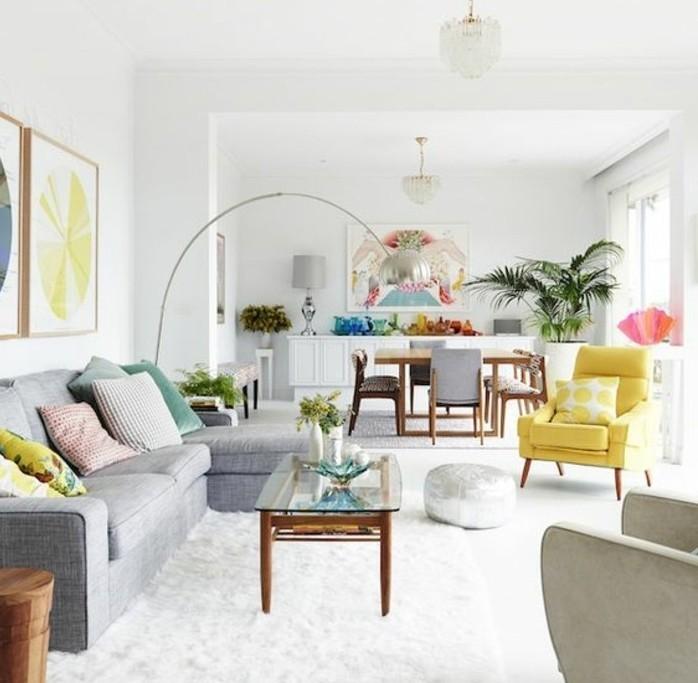 Soggiorno bianco e grigio, divano con cuscini colorati, tavolino di legno con superficie di vetro