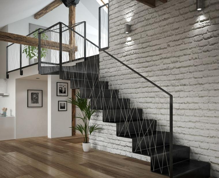 Mansarda con scale interne, pavimento in legno parquet, parete con mattoni a vista