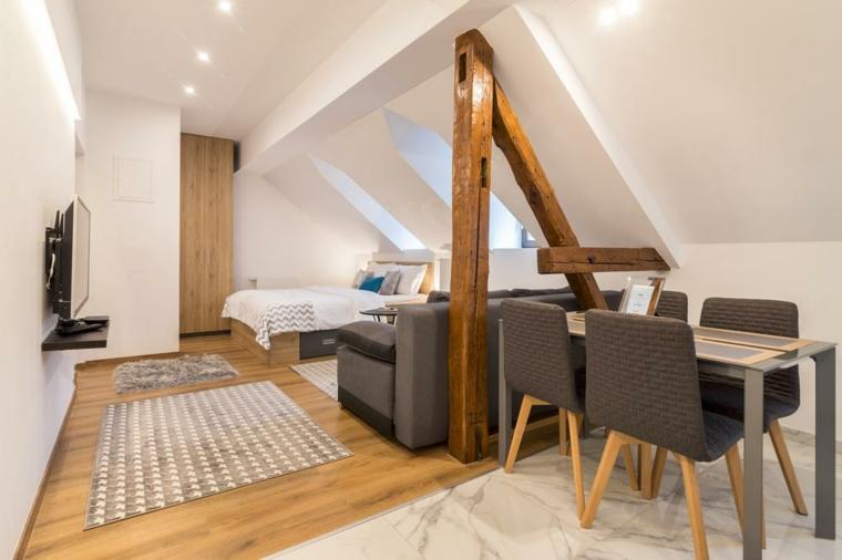 Mansarda con camera da letto, tavolo da pranzo con sedie, soffitto in pendenza