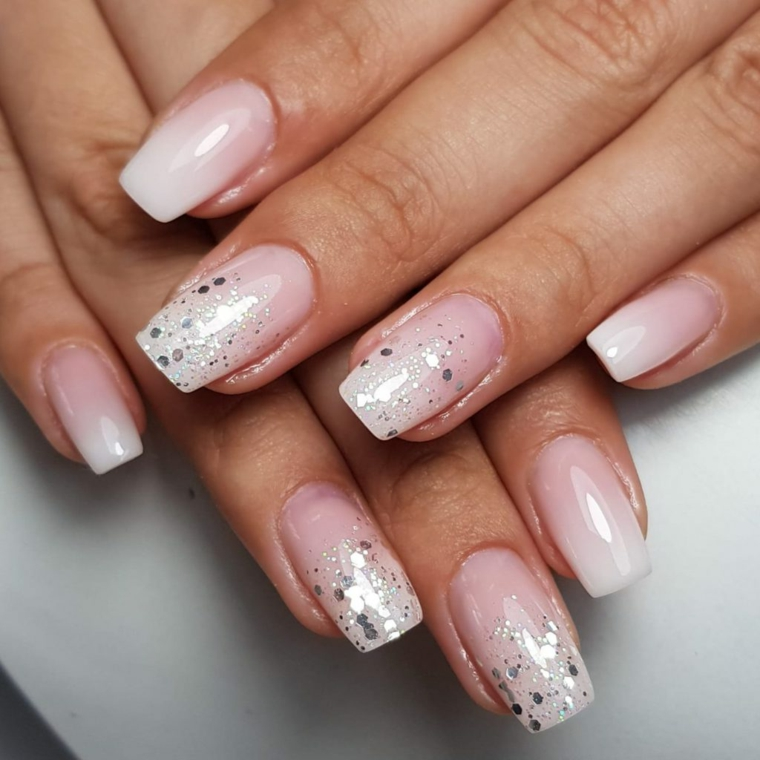 Smalto base di colore rosa, unghie decorate con glitter, mani di una donna