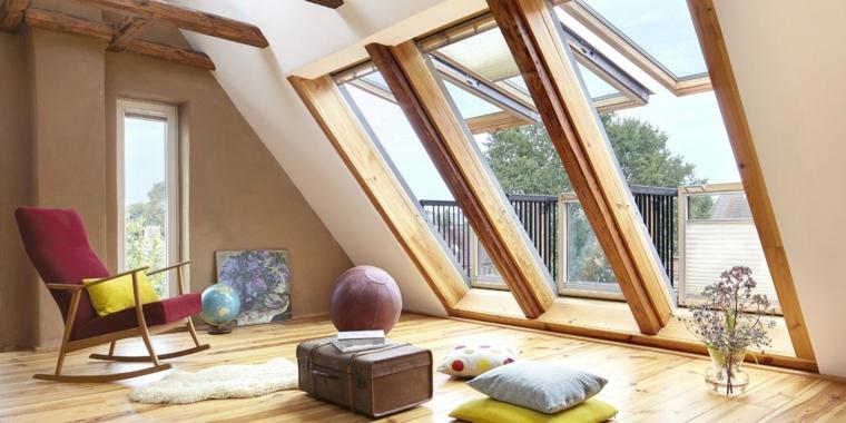 Sottotetto con vetrate, pavimento in legno, sedia a dondolo, cuscini per terra